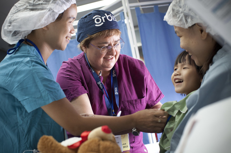 Orbis volunteer ophthalmic nurse, Cherelyn Victor, RN, works in the Flying Eye Hospital recovery room to prepare Minh, 4, for treatment during the Flying Eye Hospital's previous trip to Vietnam. Learn more: orbis.org (photo: Geoff Oliver Bugbee/Orbis).