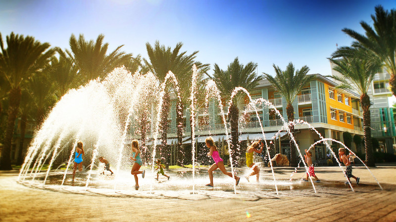 Children play in the Camana Bay fountains
