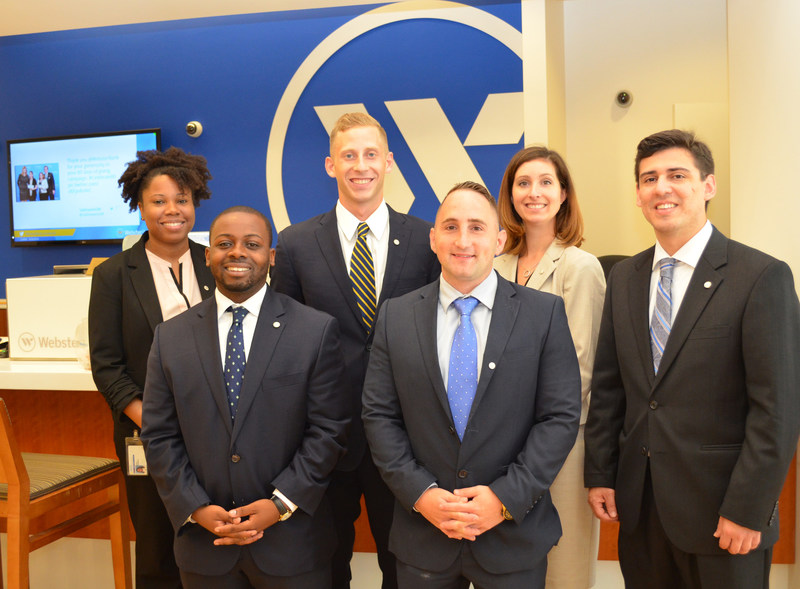 In the photo, from the left in the rear, at a Webster Bank banking center in Waterbury, Connecticut, are the following Webster bankers: Ebony Hargrove, Ian Milne, and Danielle Fernald. In front, from left: Elijah Coleman, Anthony Sidera, and Philip Thierman.
