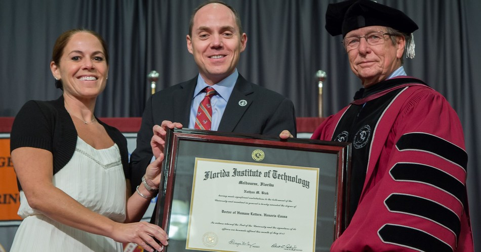Florida Institute of Technology President T. Dwayne McCay, right, presents Michael Bisk and Alison Bisk with honorary doctorate degree awarded posthumously to their father, Nathan M. Bisk, a longtime Florida Tech benefactor and pioneer of online education.