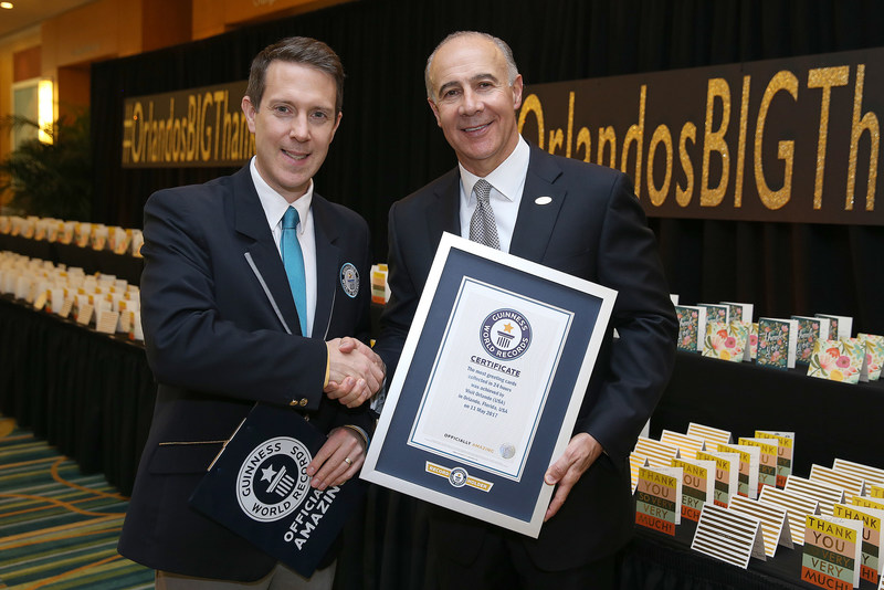 Philip Robertson, GUINNESS WORLD RECORDS adjudicator and George Aguel, President and CEO of Visit Orlando, celebrate the declaration of Visit Orlando as a GUINNESS WORLD RECORDS title holder as part of the launch of a new thank you campaign, on May 11 in Orlando, Fla. (Photo Credit: Alex Menendez)