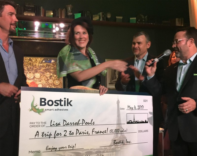"""Ted Acworth of Artaic, Mike Jenkins and Scott Banda of Bostik present DNG Grand Prize to designer Lisa Darroh-Pouls. Her mosaic creation """"Champagne Wishes"""" is behind the group."""
