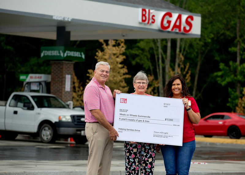 Dawn Albright, General Manager of BJ's Wholesale Club in Summerville, S.C. (right), presents a donation of a year's supply of gas and tires to Tony Fowler, chair of the board (left), and Betsy Luke, executive director (center), both of Meals on Wheels Summerville in honor of the grand opening of BJ's newest gas station.