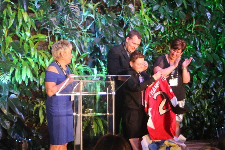 WISHES COME TRUE Colin Gillespie (centre) shows off an Ottawa Senators jersey – one of the items from his wish box –  presented by Event Coordinator, Sylvia Densmore (left), as he is applauded by his parents, James (centre) and Laurie Gillespie (right). (CNW Group/The Children's Wish Foundation of Canada)