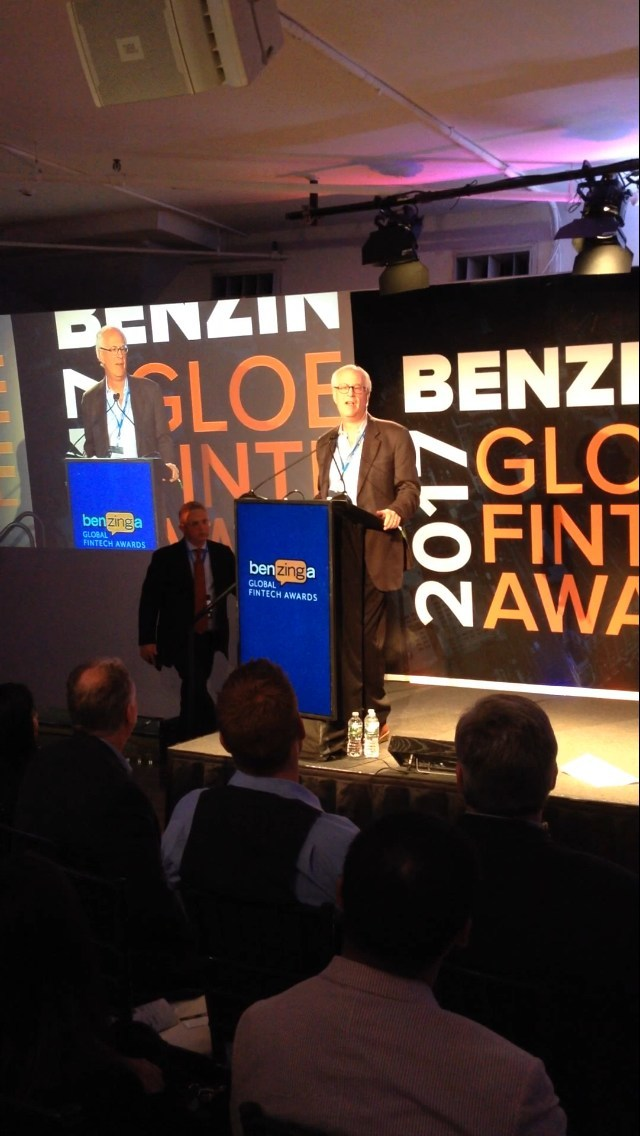 Marc Chaikin accepting Benzinga award with Jason Raznick approaching stage