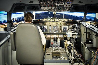 An IT specialist at the John A. Volpe National Transportation Systems Center flies a Boeing 737-800NG simulator with Aurora�s ALIAS technology demonstration system as his co-pilot. (PRNewsfoto/Aurora Flight Sciences)