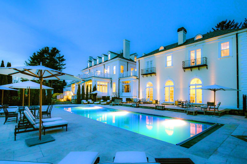 The 7-acre estate known as Sunset Hall in Ridgefield, CT will be sold at a luxury auction® on May 19, 2017. Miami-based Platinum Luxury Auctions is managing the auction sale in cooperation with listing agent Laura Freed Ancona of William Pitt Sotheby's International Realty. The property has an intriguing provenance that includes serving as home to the United Nations in 1946, and was also once owned by the brother of Harry Houdini. Pictured: The estate's pool and deck at dusk.