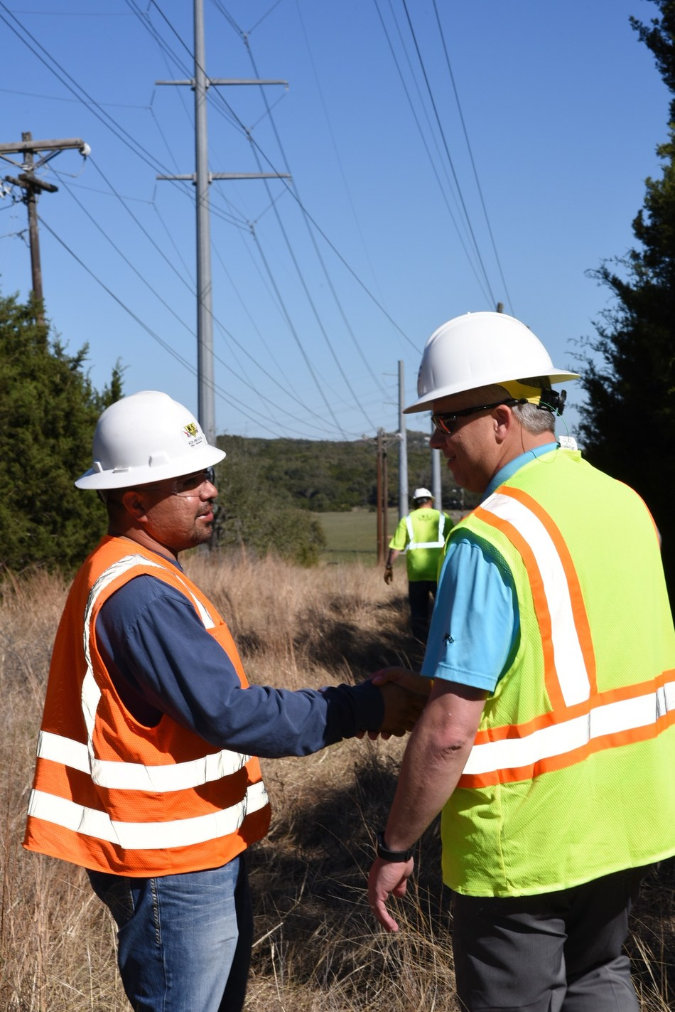 Manager of BEC Fiber, Shane Schmidt, works with a contractor to install the fiber optic cable that will upgrade Bandera Electric Cooperative's distribution system to a smart grid.