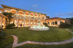 Platinum Luxury Auctions has announced the upcoming sale of this spectacular waterfront mansion located in Daytona Beach, Florida. Built and owned by the France family, the founders of NASCAR, the property offers 3.8 acres and more than 325 feet of water frontage on Daytona's Halifax River. Though not previously offered for sale, the home was appraised for $13.8 million. Discover more at RiverfrontLuxuryAuction.com. Pictured: The rear loggia and courtyard fountain at dusk.