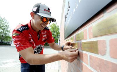 IndyCar driver Graham Rahal places the name of his military hero, his grandfather Michael Rahal, on the Crown Royal Wall of Gratitude at the Indianapolis Motor Speedway, Thursday, May 18, 2017. (Doug McSchooler/AP Images for Crown Royal)