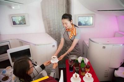 Une hôtesse de l'air servant un café Nespresso aux passagers (PRNewsfoto/Hainan Airlines Co., LTD)