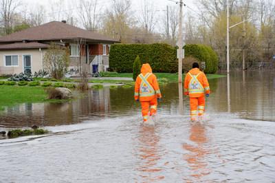 Deux employés de la Ville de Laval visitent une rue inondée. (Groupe CNW/Ville de Laval)