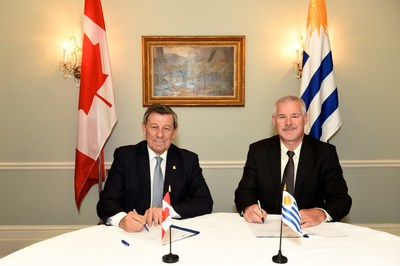 Uruguay's Minister of Foreign Affairs, Rodolfo Nin Novoa (seated left) signs agricultural food security partnership with Steve Fabijanski, President and CEO of Agrisoma Biosciences Inc. (seated right) (CNW Group/Agrisoma Biosciences Inc.)