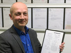 Dr. Chris Hilton, Chief Technology Officer, holding the 100th global patent recently awarded Protean Electric, the global electric drive technology company.
