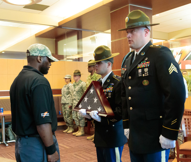 Thomas Skaggs of Pepsi accepts the flag from the United States Army Color Guard