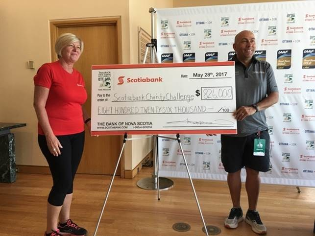 John Halvorsen, President and Race Director of Run Ottawa and Carole Chapdelaine, Scotiabank's Senior Vice President, Quebec and Eastern Ontario Region, unveil the amount raised during the Scotiabank Charity Challenge. $826,000 and counting will help 64 local and national charities. (CNW Group/Scotiabank)