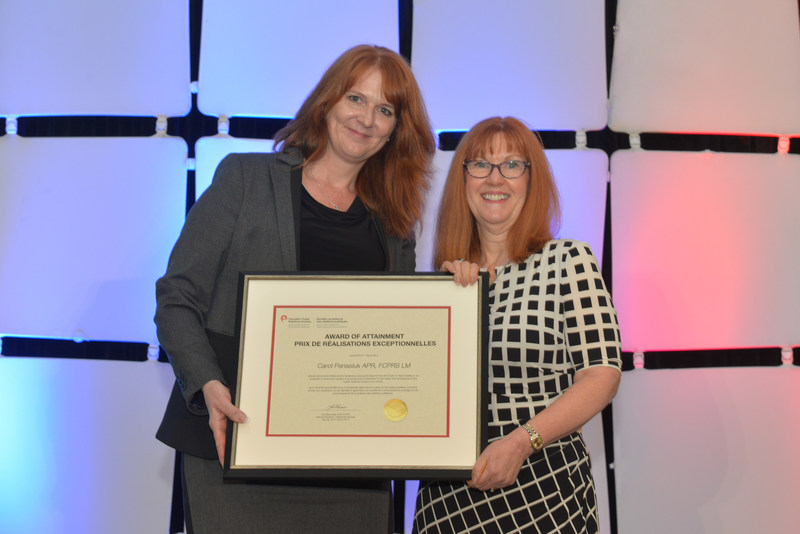 Carol Panasiuk, APR, FCPRS (right) receiving the 2017 Award of Attainment from CPRS National President Kim Blanchette, APR, FCPRS at Illuminate, the 2017 CPRS National Conference, in Kelowna B.C., May 28. (CNW Group/Canadian Public Relations Society)