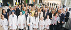 Mr. Jean Coutu and Mrs. Marcelle Coutu surrounded by their family members, Dr. Fabrice Brunet, CEO of the CHU Sainte-Justine, Dr. Michaud, Ms. Maud Cohen, the Honourable Michael M Fortier, Ms. Sophie Gravel, Mr. Ludovic Sibiude, Ms. Dorothée Sibiude and eight children from Sainte-Justine. (CNW Group/CHU Sainte-Justine Foundation)