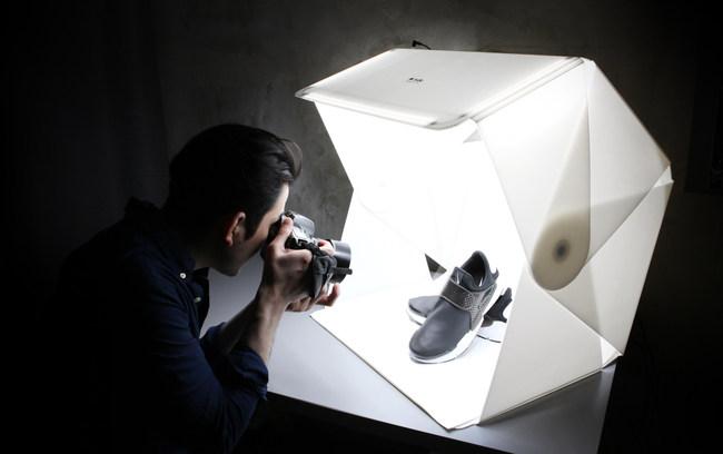 A photographer uses the Foldio3 to take a professional background-free image of fashionable shoes. (PRNewsfoto/Orangemonkie)