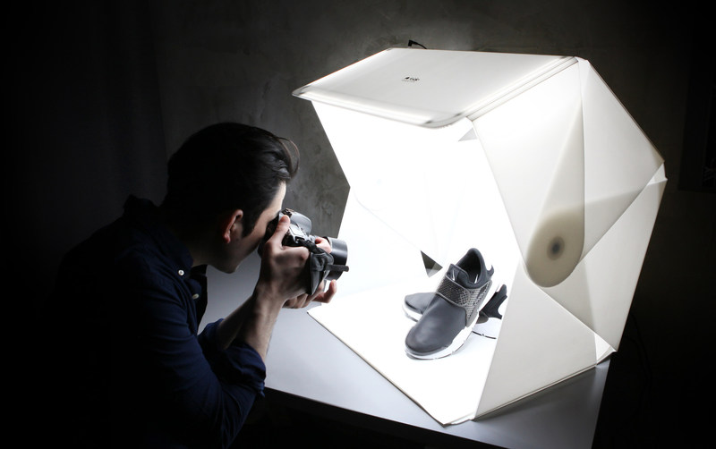 A photographer uses the Foldio3 to take a professional background-free image of fashionable shoes. (PRNewsfoto/Orangemonkie)