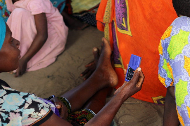 Rural Tanzanian Woman listening to the solar-powered MP3forLife Player developed by URIDU. The player contains more than 400 carefully selected answers to questions about health, nutrition, family planning, child care, work safety and many more topics.