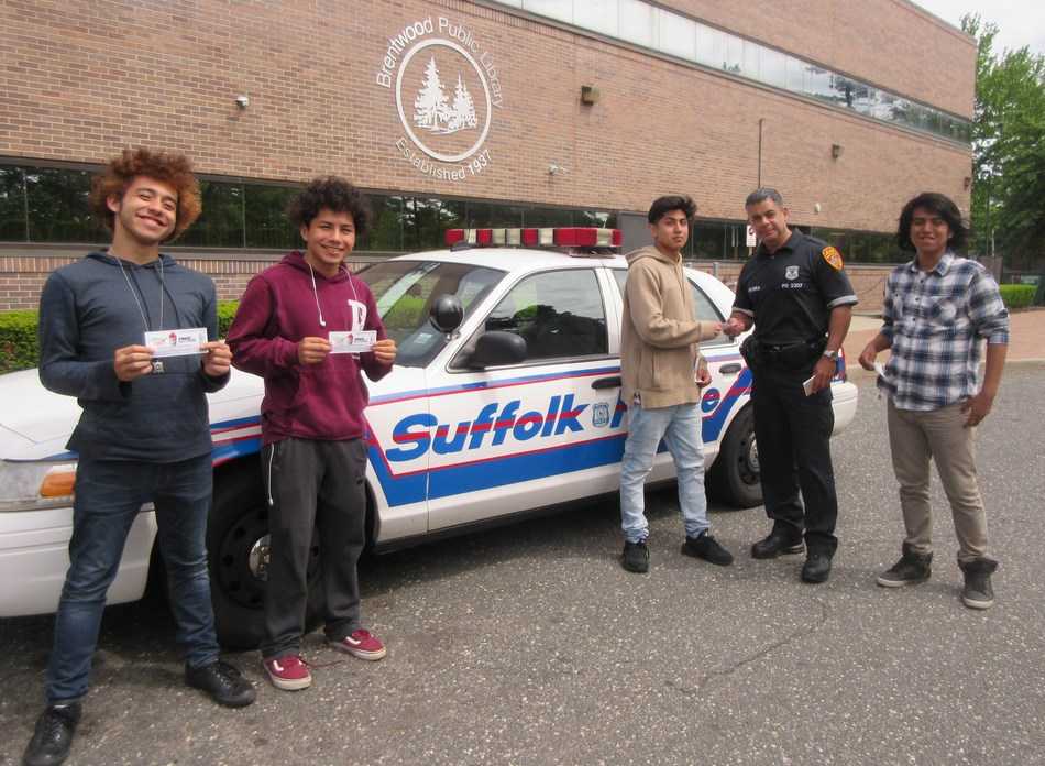 """Suffolk County, New York, police officer """"tickets"""" Brentwood High School teens for attending an after school gaming program, created in partnership with the Suffolk County Police Department and the Brentwood Public Library. The ticket, actually a 7-Eleven Operation Chill coupon good for a small free Slurpee drink, rewards the students for participating in the program that encourages relationship building between youth and local police officers."""