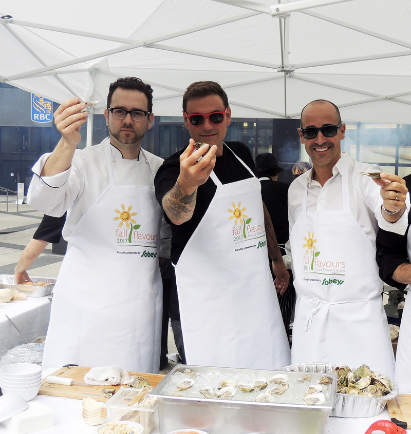 Chef Corbin, Chuck Hughes and David Rocco handing out oysters in downtown Toronto to celebrate the launch of The Fall Flavours Festival taking place on PEI in September. (CNW Group/Results Marketing & Advertising)