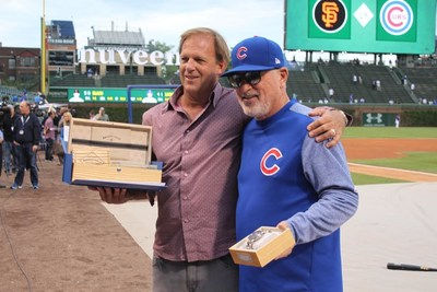 "Chicago Cubs Manager Joe Maddon is presented with ""The Wrigley Field™ Chrono: Owner's Edition"", a limited-edition collectors' Cubs watch featuring wood from original Wrigley Field™ ballpark seats, at a pregame ceremony tonight to celebrate the World Champion's 1000th victory. [Pictured from left]: Paul Buss, CEO of Original Grain Watch Co.; and Chicago Cubs Manager Joe Maddon.  (Photo courtesy of the Chicago Cubs)."