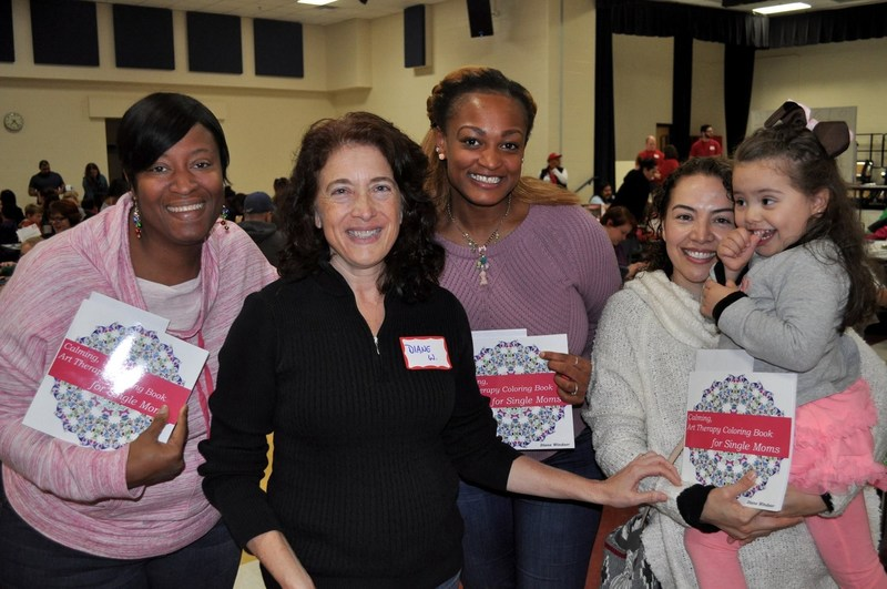 Diane Windsor, with some of the single moms from the Single Side UP support group. They are displaying the coloring book for single moms, published by Motina Books.
