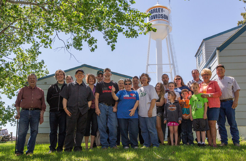 "Ryder, N.D. residents gather in front of the town's newly refurbished water tower, which has become a landmark for motorcycle riders in the Dakotas. To launch riding season, Harley-Davidson will ride into Ryder Saturday, June 3 with the aim of creating the first fully motorcycle licensed town. To commemorate the experience, Ryder city officials will change the town's name to ""Riders"" this riding season."