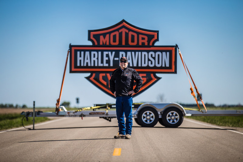 "Mayor of Ryder, N.D., Jody Reinisch, poses on Highway 28 leading into town. To launch riding season, Harley-Davidson will ride into Ryder Saturday, June 3 with the aim of creating the first fully motorcycle licensed town. Ryder city officials will change the town's name to ""Riders"" this riding season to commemorate the experience."