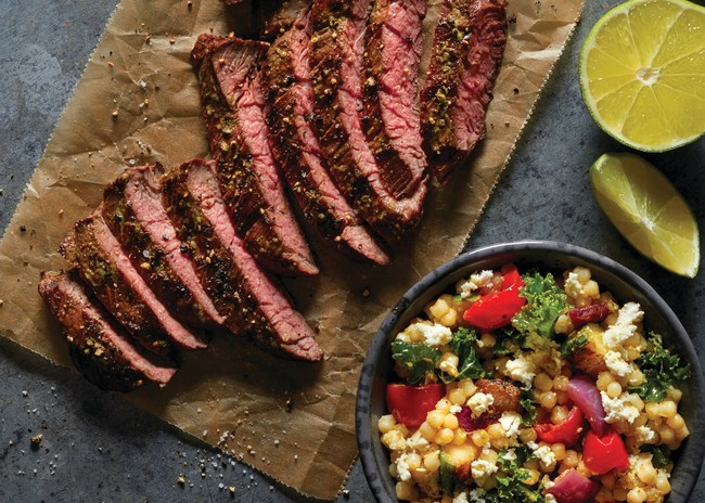 New York Strip Steak with pearled couscous pilaf, grilled zucchini, red onions, tomatoes, kale, Feta and Poblano vinaigrette