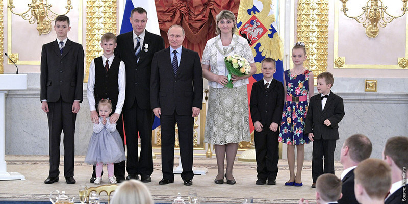 """Russian President Vladimir Putin awarded the Order of """"Parental Glory"""" to Valeriy and Tatiana Novik, Jehovah's Witnesses from Karelia, during a ceremony in Moscow at the Kremlin. Six of their eight children are shown in the photo."""