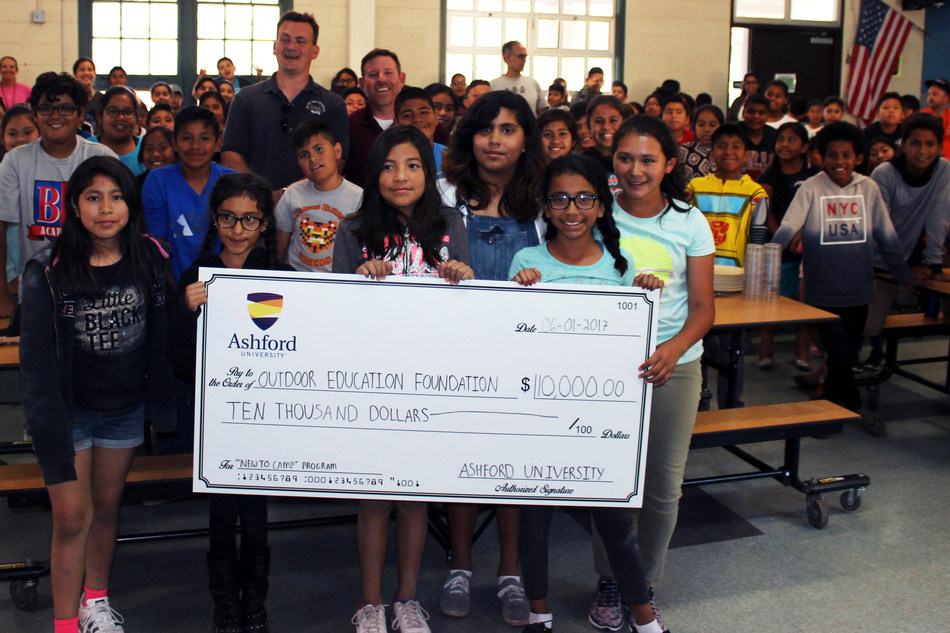 """Students from San Marcos Elementary School holding Ashford University's $10,000 donation to the San Diego County Outdoor Education Foundation's """"New to Camp"""" program."""