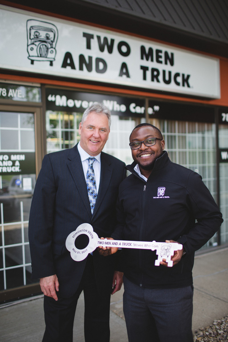 Owner/General Manager George Nwajiaku accepts the key to his Edmonton South franchise from Two Men And A Truck - Canada's President John Prittie. Photo: Carmyn Joy Effa Photography (CNW Group/Two Men and a Truck)