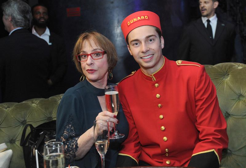 Patti LuPone enjoys a glass of champagne alongside Cunard bellman.