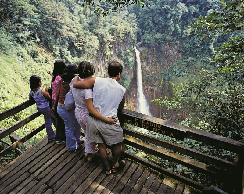 Family enjoys an impressive waterfall view at Río Cuarto, Costa Rica.