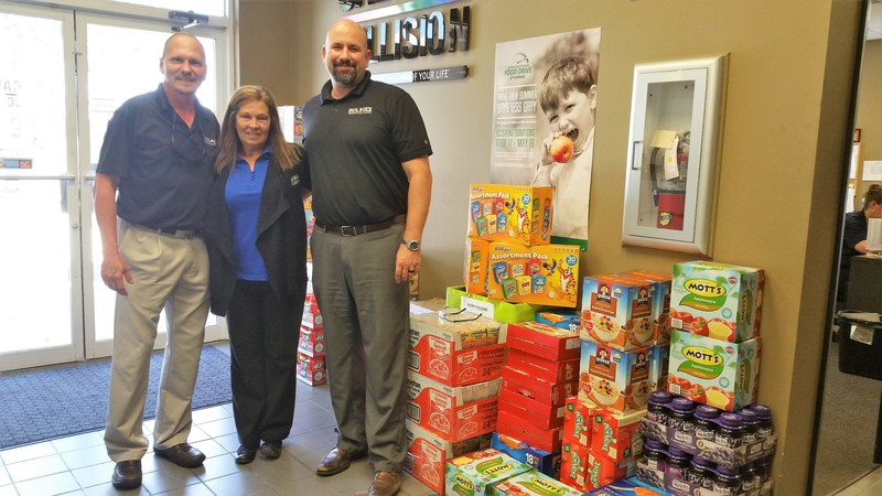 Caliber Collision associate Mary Carter in Tampa, Florida, thanks Rob Anderson and Mike Harvey, representatives from business partner LKQ Corporation, for their generous contribution to the 6th Annual Rhythm Restoration Food Drive.