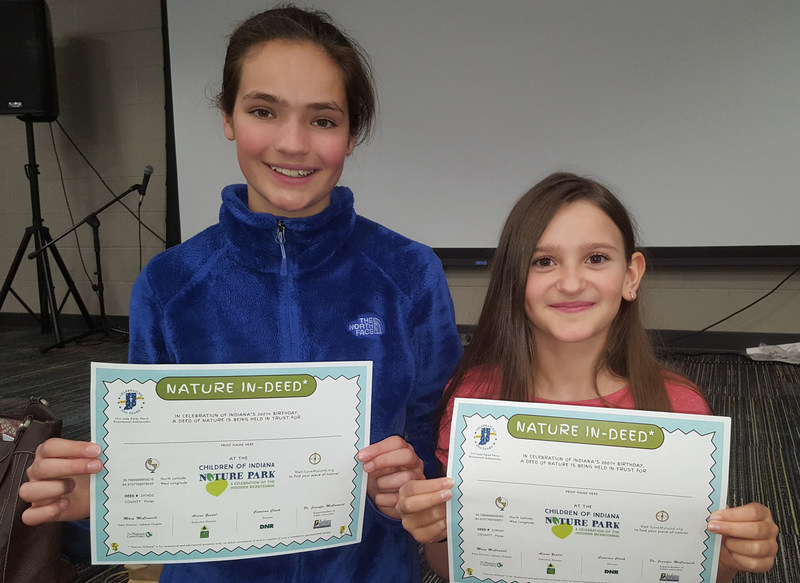 Kate Weber and Angela Coulopoulos, students at Cooks Corner Elementary in Valparaiso, Ind., receive deeds to their own plots of land at the new Children of Indiana Nature Park.