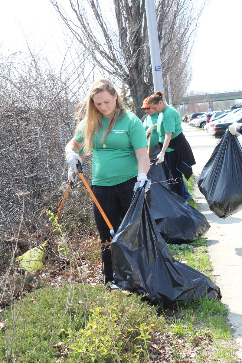 Volunteers at The Nature's Bounty Co. pick up trash in support of Earth Day at the Ronkonkoma, NY LIRR station.