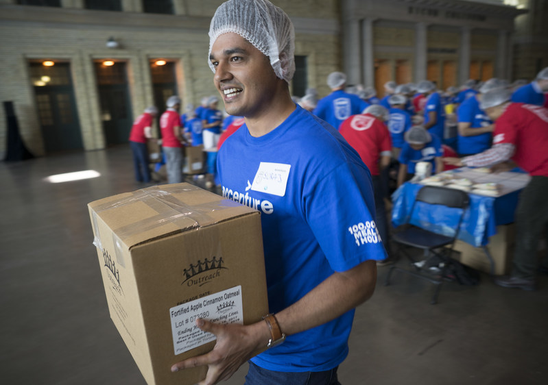 Accenture employee Suraj Bhardwaj adds a box of hunger relief packages to the pile of 15,200 pounds of food packed and donated to the Daily Bread Food Bank during Accenture's annual employee meeting in Toronto, Ont. on Friday, June 16, 2017.   A total of 100,000 meals and $10,000 were donated by Accenture.  The Canadian Press Images PHOTO/Accenture (CNW Group/Accenture)