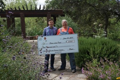 Feed a Bee steering committee member Billy Synk of Project Apis m. presents a check to Placer Land Trust and the School Park Community Garden in Auburn, California.