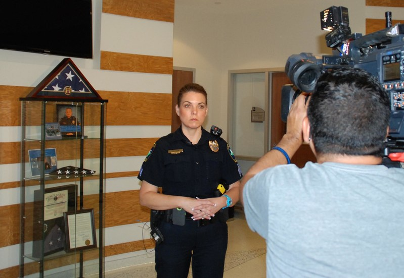 Following gifts of Thin Blue Line Shields of Strength given by Atlanta-based nonprofit, Point 27, to the Little Elm, Texas Police Department Monday, Sgt. Nicole Shaw prepares to do a television interview in the public safety center, in front of a display case with mementos honoring a fellow- and fallen-officer Detective Jerry Walker. Walker was shot in the line of duty January 17.