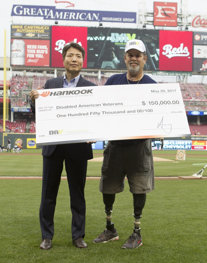 Hankook Tire America Corp. Senior Vice President Jae Bum Park presents DAV National Commander Dave Riley with a $150,000 check during an on-field check presentation at the Cincinnati Reds Military Appreciation Day Game at the Great American Ball Park on May 20. Hankook has renewed its partnership with DAV to continue to help veterans through mobility and provide free services to veterans of all generations where they live.