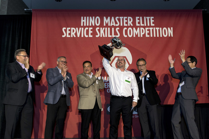 Billy Stanley of Rush Truck Center - Houston raises the cup as the winner of Hino Truck's 2017 National Master Elite Service Skills Competition.
