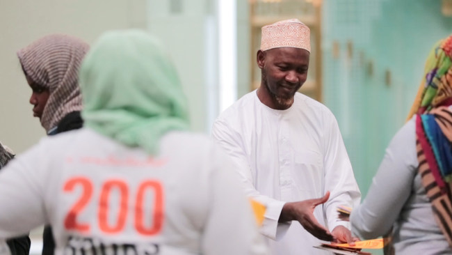 """Imam of The Islamic Cultural Center of New York, Chernor S. Jalloh receiving cards from DoSomething.org & buildOn students for """"Sincerely, Us"""" campaign. Photo Credit: Chris Alfonso for DoSomething.org"""
