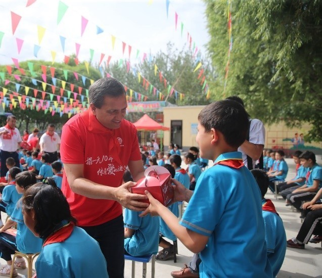 Micky Pant, Yum China CEO, with students from Ye Yi Li Gan Elementary School in Xinjiang