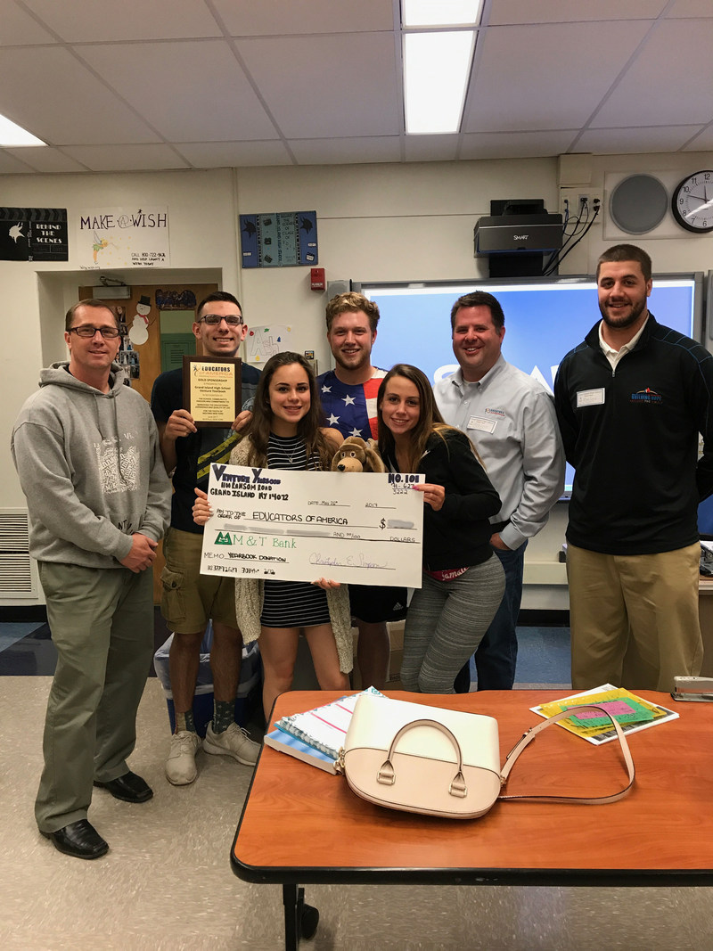 Adviser Mr. Simpson and his senior staff donate to Educators of America to build a computer lab for younger children to access new resources.