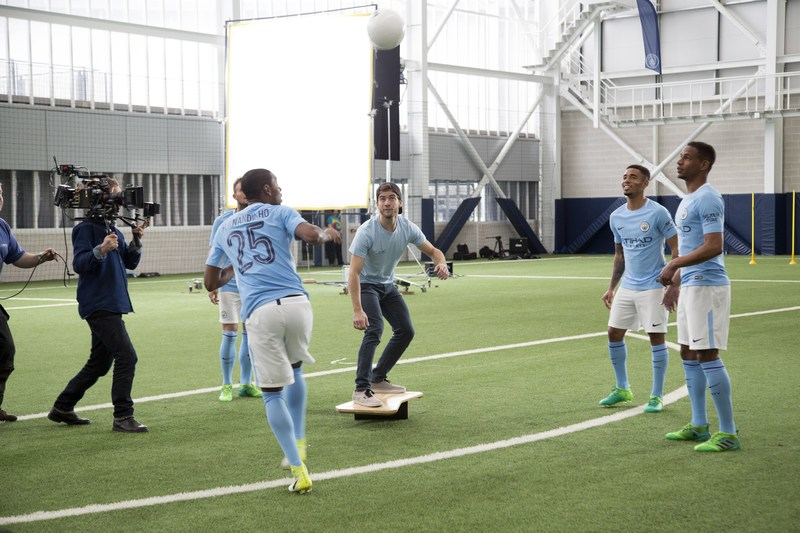 Gabriel Pacca from Woo the Boards practices his balance with Manchester City players during Wix's commercial shoot