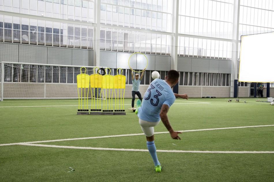 """El jugador del Manchester City, Gabriel Jesus, pone a prueba el equilibrio de Gabriel Pacca durante la grabación del comercial de Wix y """"Woo the Board."""""""